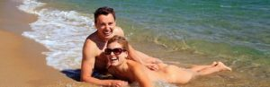 Young caucasian couple sunbathing at the beach